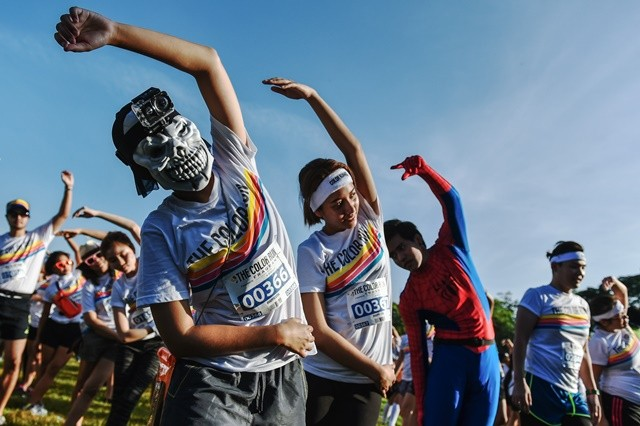 Participants of the Color Run Bangkok do warm-up exercises at the Suan Rod Fai park in Bangkok, Thailand, on Oct. 31, 2015. The Color Run is a 5km public paint race that originated in the U.S. in 2011. In a typical Color Run race, participants will end up covered in a mixture of colored powders made from corn starch. (Xinhua/Li Mangmang)