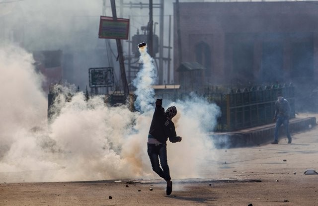 A Kashmiri Muslim protester throws an exploded tear smoke shell back at Indian police and paramilitary troopers (unseen) during a protest in Srinagar, summer capital of Indian-controlled Kashmir, Oct. 30, 2015. Kashmiri Muslim protesters clash with Indian police and paramilitary troopers after Friday prayers over the killing of Abu Qasim, a top militant commander heading Lashkar-e-Toiba (LeT) in restive Indian-controlled Kashmir. (Xinhua/Javed Dar)