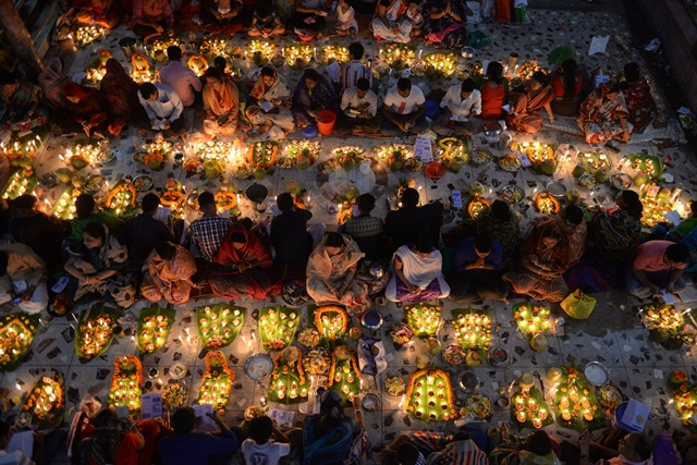 Bangladeshi Hindu devotees light candles and pray at a temple during the Rakher Upobash, a Hindu religious fasting festival in Dhaka, Bangladesh, Nov. 10, 2015. Hindu devotees fast and pray in earnest to the gods for their favours during the ritual called Kartik Brati or Rakher Upobash traditionally. (Xinhua/Shariful Islam)