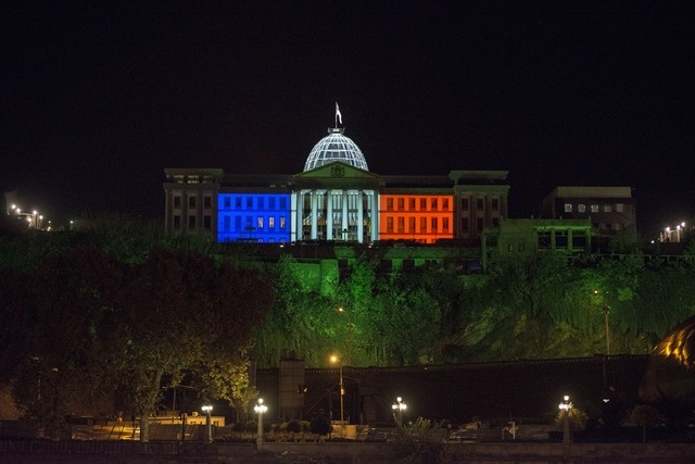 Georgia's Presidential Palace is illuminated in the colors of blue, white and red as people mourn for the victims of the terrorist attacks in Paris, in Tbilisi, capital of Georgia, on Nov. 14, 2015. (Xinhua/Giorgi Induashvili)