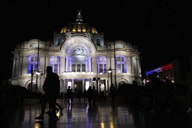 People walk in front of the Fine Arts Palace illuminated with the colors of the French national flag to mourn for the victims of the terrorist attacks in Paris, in Mexico City, capital of Mexico, Nov. 14, 2015. (Xinhua/Pablo Ruiz) (zjy)