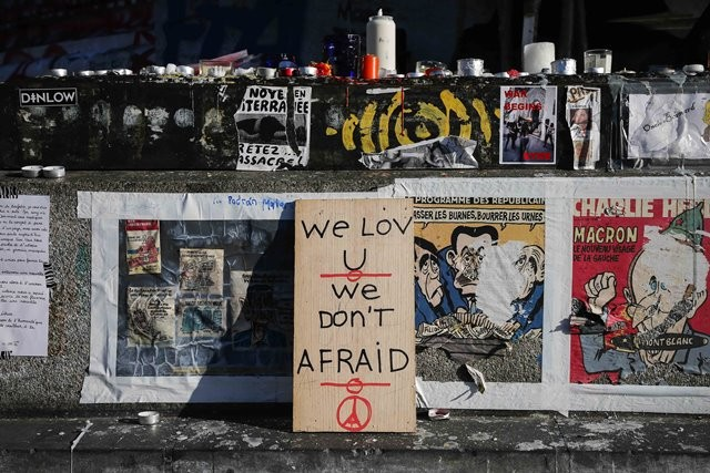 """People place candles and a placard reading """"We don't afraid"""" at the Place de la Republique square to mourn for the victims of the terrorist attacks in Paris, capital of France, Nov. 15, 2015. (Xinhua/Zhou Lei)"""