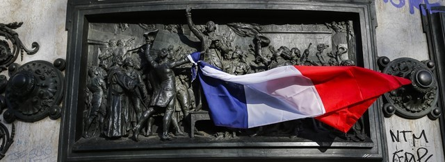 People tie a French national flag to the monument at the Place de la Republique square to mourn for the victims of the terrorist attacks in Paris, capital of France, Nov. 15, 2015. (Xinhua/Zhou Lei)