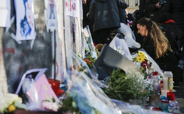 People present flowers at the Place de la Republique square to mourn for the victims of the terrorist attacks in Paris, capital of France, Nov. 15, 2015. (Xinhua/Zhou Lei)(azp)