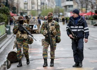 """Belgian soldiers and a policeman patrol in central Brussels, capital of Belgium, on Nov. 22, 2015. The terror threat level in the Brussels region was increased to """"maximum"""" as authorities received information on the risk of an attack """"similar to Paris."""" The terror threat currently facing Belgium is """"broader than Salah Abdeslam alone"""", the country's interior minister Jan Jambon said in a TV interview late Saturday. (Xinhua/Zhou Lei)"""