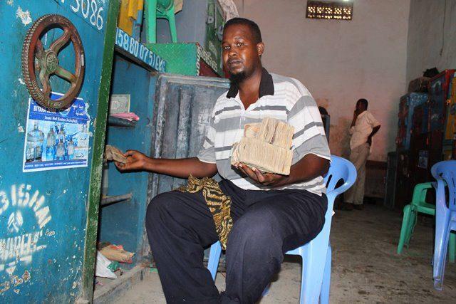 A man displays money at the exchange market in Suq Bacad market in Mogadishu, capital of Somalia, Nov. 18, 2015. (Xinhua/Faisal Isse)