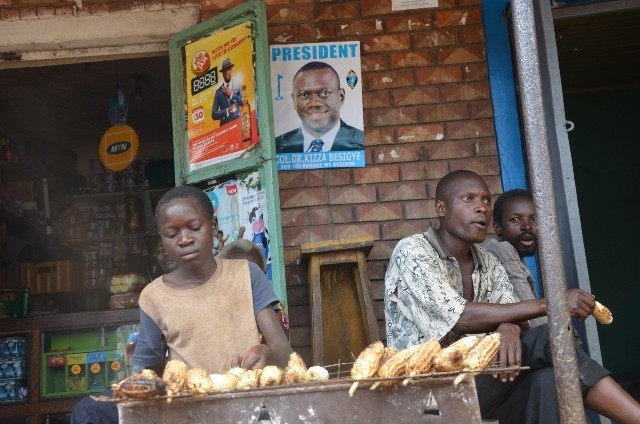 A boy (L),is seen roasting  maize next to a poster of the Forum for Democratic Change (FDC) presidential candidate Kizza Bessigye, at Bugusege trading centre in Sironko district, eastern Uganda, Nov. 23, 2015. Uganda goes to the polls in mid-February 2016, with rampant unemployment rates in the country. (Xinhua/Daniel Edyegu)