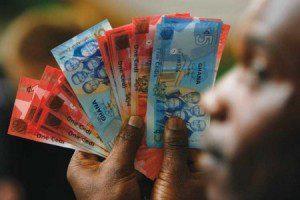 wpid-man-holding-ghanaian-money.jpg