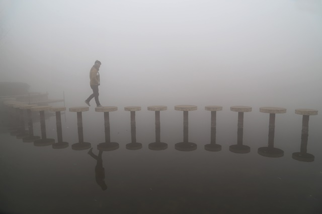 Photo taken on Dec. 23, 2015 shows a man walking in smog in Zixia Park, Wenxian County, central China's Henan Province. (Xinhua/Xu Hongxing)