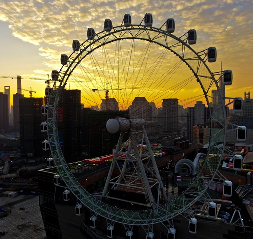 An aerial photo taken on Dec. 19, 2015 shows the panorama of a sky wheel built on a roof in Shanghai, east China. (Xinhua/Shen Chunchen)