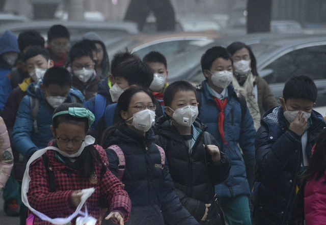 Students wearing masks walk on a smog-shrouded street for a school event in Beijing, Dec. 25, 2015. (Xinhua/Wu Wei)