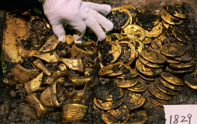 Photo taken on Dec. 24, 2015 shows gold cakes unearthed from the main coffin in the Haihunhou (Marquis of Haihun) cemetery, east China's Jiangxi Province. There were 96 gold cakes and several hoof-sahped golds newly unearthed between the inner and external coffin at the Haihunhou cemetery on Dec. 24, making the number of gold cakes unearther here rise to 285, the most among all archaeological excavations of the Han Dynasty (206 B.C.-220 A.D.) tombs. (Xinhua/Wan Xiang)