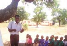 Kaase Primary School teacher teaching Kindergarten children under a tree
