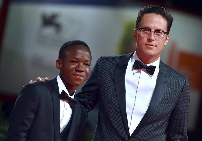 epa04911700 US director Cary Fukunaga and Ghanaian actor/cast member Abraham Attah (L) arrive for the premiere of 'Beasts of no nation'' during the 72nd annual Venice International Film Festival, in Venice, Italy, 03 September 2015. The movie is presented in the official competition 'Venezia 72' at the festival running from 02 to 12 September. EPA/ETTORE FERRARI