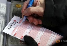 A woman fills out a ticket for the $700 million Powerball lottery draw at Times Square in the Manhattan borough of New York January 7, 2016. REUTERS/Shannon Stapleton
