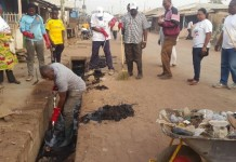 Alhaji Collins Dauda, Minister of Local Government and Rural Development and Alhaji Muhammad Bawa Braimah, Municipal Chief Executive desilting the gutters whiles other people are also working.
