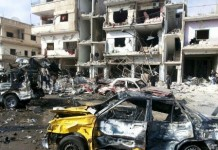 People inspect the site of a two bomb blasts in the government-controlled city of Homs, Syria on 21 February.REUTERS/SANA