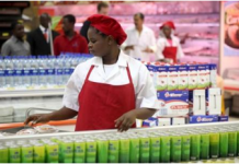 """A shop assistant arranges products at the South African firm Shoprite""""s main store in Nigeria""""s commercial capital Lagos"""