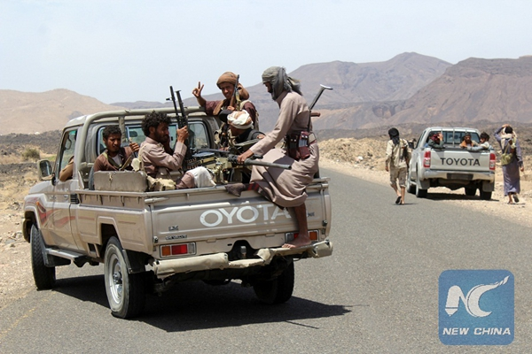 Yemeni fighters loyal to exiled President Abd-Rabbu Mansour Hadi wait in their pick-up trucks on a road in the Sirwah area, in Marib province on April 9, 2016. [Xinhua]