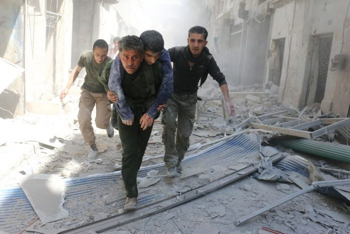 Syrians evacuate an injured man following an air strike on a rebel-held neighbourhood in the northern Syrian city of Aleppo on April 29, 2016 (AFP Photo/Ameer Alhalbi)