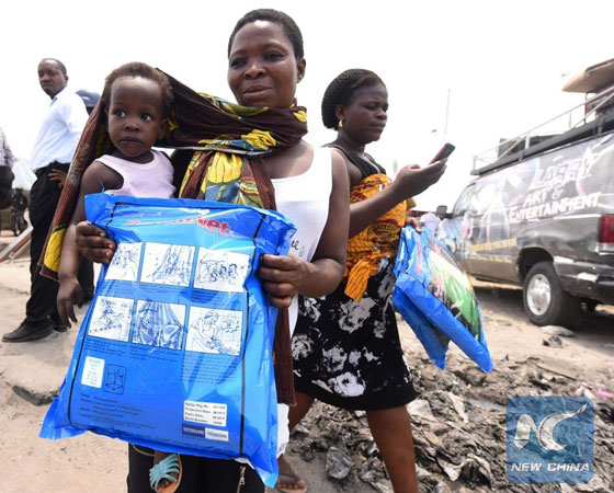 A woman carrying a baby holds a treated mosquito net during a malaria prevention action at Ajah in Eti Osa East district of Lagos, on April 21, 2016. [Photo/Xinhua]