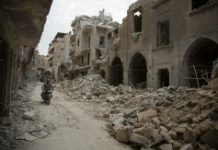 AFP / Karam Al-Masri A Syrian man rides his motorbike past destroyed buildings on May 2, 2016, in Aleppo's Bab al-Hadid neighbourhood which was targeted recently by regime air strikes