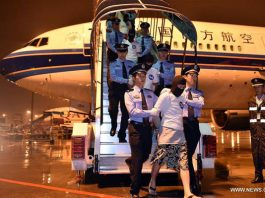 Chinese telecom fraud suspects are escorted off an aircraft by the police at Guangzhou Baiyun International Airport in Guangzhou, capital of south China's Guangdong Province, April 30, 2016.(Xinhua/Liang Xu)