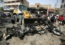 AFP / Agmad Al Rubaye A bulldozer clears the wreckage following a car bomb attack in Sadr City, a Shiite area north of the capital Baghdad, on May 11, 2016