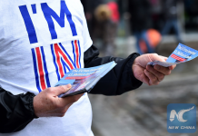 """A campaigner with Britain Stronger in Europe, the official """"Remain"""" campaign for the forthcoming EU referendum, hands out leaflets in central London on April 15, 2016. (Xinhua/AFP)"""