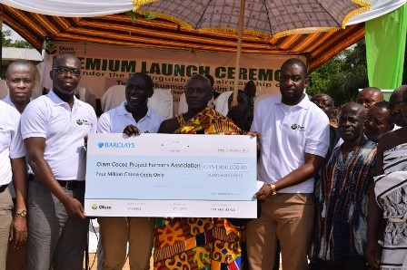 From extreme left: Mr Kennedy Ntoso, Head of Cocoa Sustainability, Mr Kenneth Antwi, Head of HR, Mr Eric Asare Botwe, Head of Cocoa LBC Business and Mr Jonathan Quaynor, Head of Procurement (right in white lacoste), all of Olam Ghana, are joined by Omanhene of Wasa Amenfi Traditional Area – Nana Tetrete Okuamoah Sekyim II (middle) to display the cheque for the premium payments.