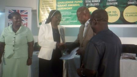Mr Samuel Okudzeto Ablakwah, Deputy Minister in charge of Tertiary Education presenting the grant pack to Reverend Sister Elizabeth Amoako-Arhen, Principal of OLA College of Education and the President of National Conference of Principals of Teacher Training Colleges (PRINCOF).