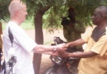 Professor Laurence David Gruer, presenting the brand new motorbike the District Coordinating Director, Alhaji Mahammed Issahaku.