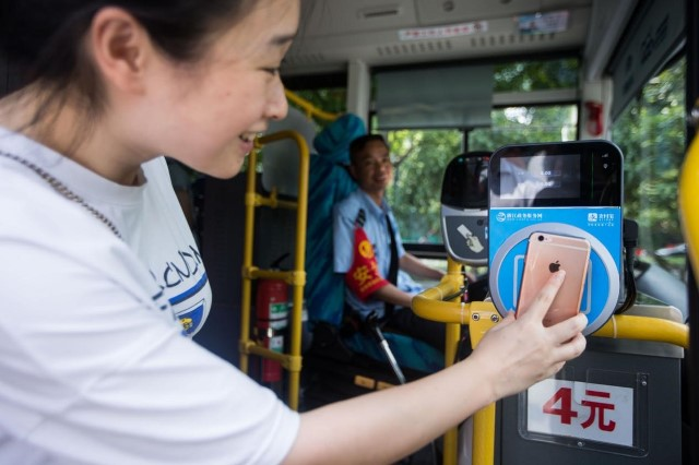 August16, a passenger boards a bus using Paypal. (CFP)