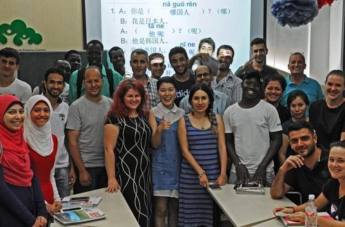 Aug.8, 2016,the teacher of traning course for foreign business personnel, ChenDan is taking group photo with her foreign students.(Xinhua)