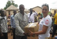 Madam Murielle Maupoint, the Executive Director of Hope for Children presenting the teaching and learning materials to Mr Mohammed Awal, the Head Master of Nemton-Kurugu E/A primary.