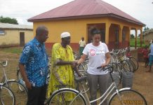 Madam Murielle Maupoint, the Executive Director of Hope for Children presenting the bicycles to Mr Goshiman Mahadu, a Traditional leader of Nanton-Kurugu Community. Looking on is Mr Tijani Hardi, the Executive Director of RAINS.