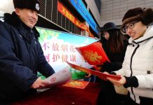 A campaign to advocate no use of fireworks for sake of less air pollution was held in Dongcheng District, Beijing in January. The picture taken shows a public security officer introducing the significance of less fireworks. (Photo by He Yong from People's Daily)