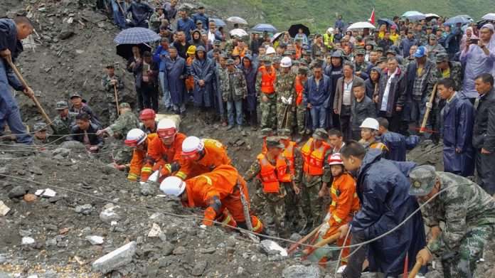 People search for survivors at the site of a landslide in the Sichuan province of China on Saturday [Reuters]