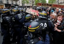 """French riot police surround demonstrators who hold a placard with the message, """"The State is not an Company"""", the day after the country went to the polls, in Paris, France, May 8, 2017. REUTERS/Jean-Paul Pelissier"""