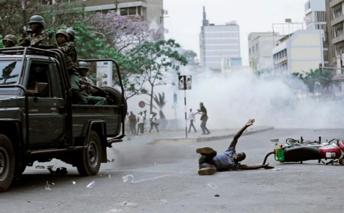 A supporter of Kenyan opposition National Super Alliance (NASA) coalition, lies on the ground after he was hit by a police truck during a protest along a street in Nairobi.