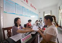 """An employee working with the """"one-stop"""" health care settlement center in Wan'an county, Jiangxi Province is handling the settlement procedures for impoverished household, August 7, 2017. (Photo by People's Daily Online)"""