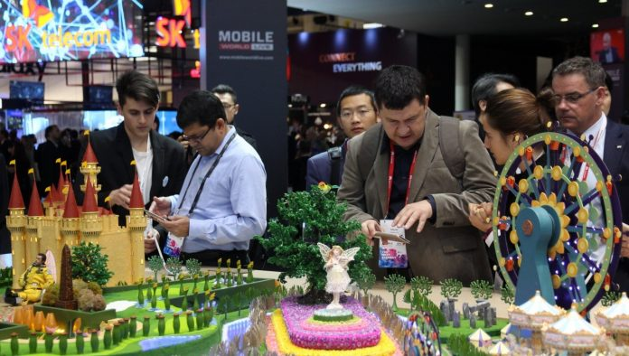 Visitors try newly-released smart phones made by Chinese manufacturer ZTE at the Mobile World Congress held in Barcelona, Spain in February, 2017. (Photo by Wang Di from People's Daily)