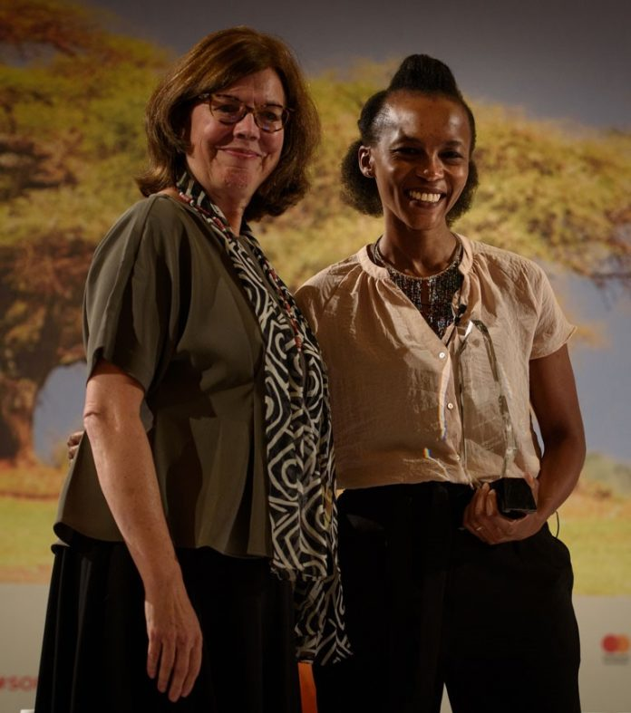 Ann Miles, Director of Financial Inclusion at the Mastercard Foundation, presents the award to Buhle Goslar of Jumo
