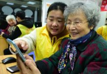 An 80-year-old woman named Ge Yuqi is learning how to use social application WeChat with the help of a volunteer on January 16, 2018. (Photo by Shi Yucheng from People's Daily Online)