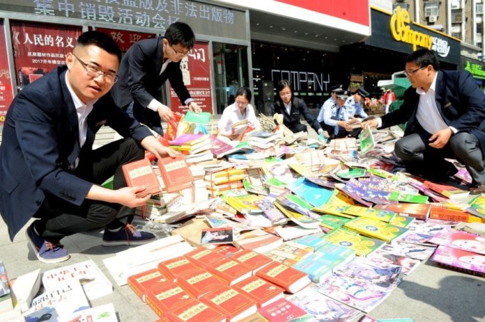 Law enforcement staff show copies of pirated dictionaries, textbooks and teaching materials confiscated at a cultural market in Huainan, Anhui province, Apr. 24, 2017. (Photo from People's Daily Online)
