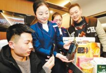 """A passenger scans a QR code to make a purchase on a train, February 7, 2018. Payments through WeChat, Alipay and other mobile payment channels are available on many Chinese trains during the 2018 """"Chunyun"""", or Spring Festival travel rush. (Photo: CFP)"""