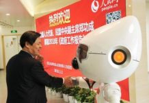 People's Daily Online's artificially intelligent robot Wangzai shakes hands with a guest at the two sessions. (Photo by Jiang Jianhua from People's Daily Online)