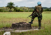 UN Photo/Staton Winter: A peacekeeper from Ghana stands guard during a senior UN official's visit to Cestos City in 2012. Some 16,000 peacekeepers from over a dozen countries served in Liberia from 2003 to 2018.