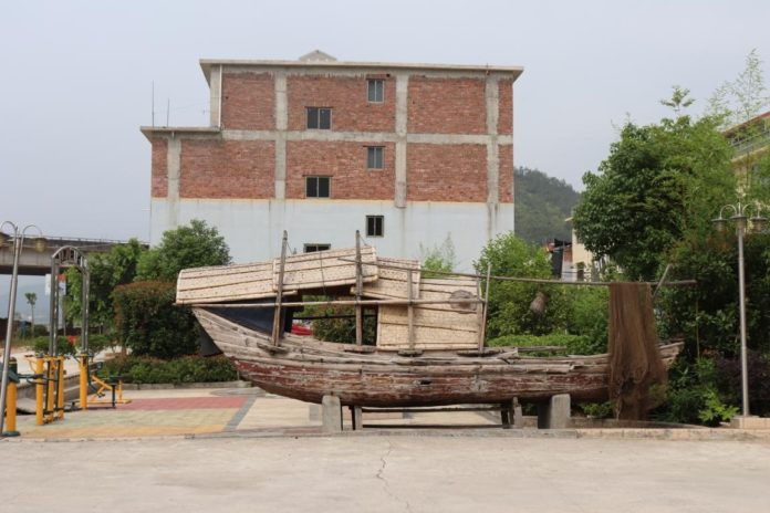 Photo shows a shabby boat placed on the Xipi Village square. Photo by Liu Lingling