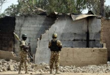 Soldiers looks at burnt house on February 4, 2016 during a visit to the village of Dalori village, some 12 kilometres from Borno state capital Maiduguri, northeastern Nigeria, after an attack by Boko Haram insurgents on the village left at least 85 people dead on January 30, 2016. At least 85 people died when Boko Haram insurgents stormed and torched a village on January 30 near the restive northeast Nigerian city of Maiduguri, a state commissioner said on February 1, 2016. Boko Haram, which seeks a hardline Islamic state in northern Nigeria, has killed some 17,000 people and forced more than 2.6 million others to flee their homes since 2009. / AFP / STRINGER (Photo credit should read STRINGER/AFP/Getty Images)